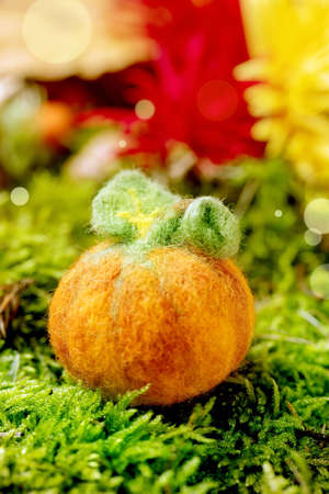 Wool needle felting Halloween pumpkin on moss with autumnal background. Fall seasonal Halloween greeting Stock Photo