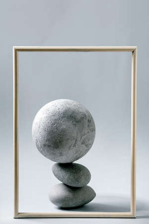 Abstract background with composition of balanced grey geometric objects sphere, picture frame and stones. Copy space. Modern concept for product presentation.