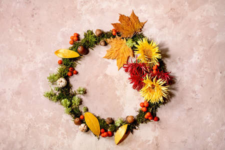 Beautiful Autumn botanical wreath composition creative layout with flowers, moss and yellow autumn leaves over beige concrete background. Flat lay, copy space Stock Photo