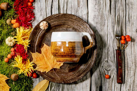 Autumn holidays table setting. Empty craft ceramic plate and mug on old wooden table decorated by fall yellow leaves, autumn berries, moss and flowers. Flat lay, copy space Stock Photo