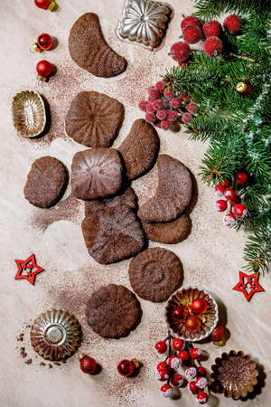 Homemade traditional Christmas shortcrust cookies chocolate crescents with cocoa icing sugar with cookie molds, fir tree, red xmas stars decorations. Pink marble background. Flat lay 写真素材 - 158562202
