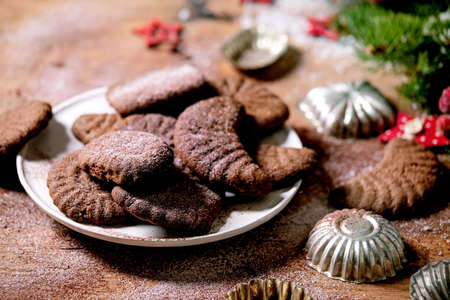 Homemade traditional Christmas shortcrust cookies chocolate crescents with cocoa icing sugar in ceramic plate with cookie molds, fir tree, red xmas stars decorations over wooden background. Close up