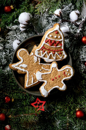Homemade traditional Christmas gingerbread cookies with icing ornate. Gingerbread Man, angel, bell on ceramic plate with xmas decorations and fir tree as background. Flat lay