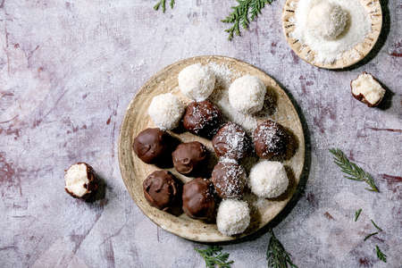 Raw vegan homemade coconut chocolate candy balls with coconut flakes in ceramic plate over white wooden background. Flat lay, copy space
