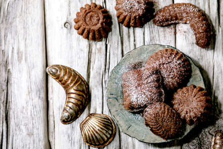 Homemade traditional shortcrust cookies chocolate crescents with cocoa icing sugar in ceramic plate with cookie molds over old wooden background. Flat lay, space