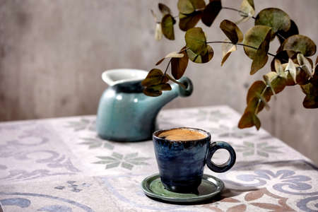 Cup of turkish black frothy coffee on ornate ceramic table with coffee pot cezve and Eucalyptus branches. Sunlight