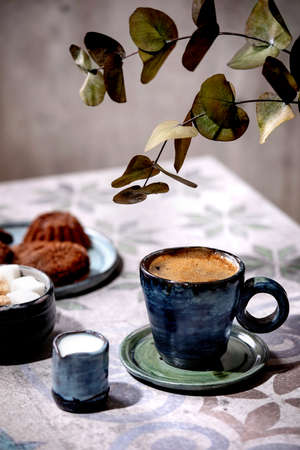 Cup of turkish black coffee with milk, sugar cubes and cookies on ornate ceramic table with Eucalyptus branches. Sunlight, shadows