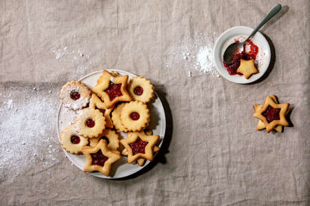 Homemade traditional Linz shortbread biscuits cookies with red jam and icing sugar on ceramic plate over linen tablecloth. Flat lay, space