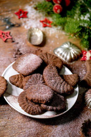 Homemade traditional Christmas shortcrust cookies chocolate crescents with cocoa icing sugar in ceramic plate with cookie molds, fir tree, red xmas stars decorations over wooden background.