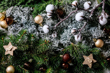 Christmas New year greeting card background with fir tree branches, moss, golden balls and stars. Top view
