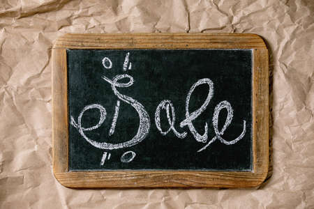 Promotion sale concept. Vintage chalkboard with hand written chalk lettering Sale with percents over craft crumpled paper. Flat lay.