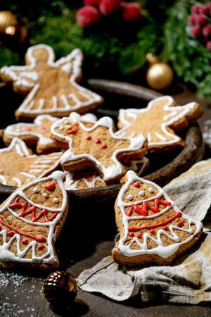 Homemade traditional Christmas gingerbread cookies with icing ornate. Gingerbread Man, angel, bell on ceramic plate with xmas decorations over dark background.