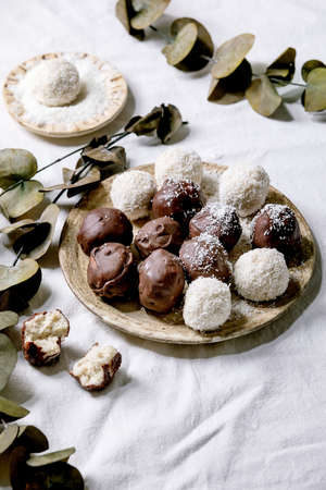 Raw vegan homemade coconut chocolate candy balls with coconut flakes in ceramic plate over white textile background with eucalyptus branches.