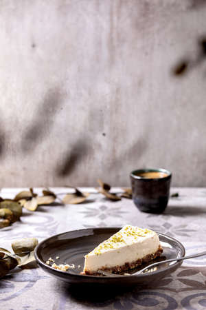 Piece of raw vegan cheesecake, no bake gluten free, decorated by lime zest and cashew nuts on plate. Cup of black coffee and Eucalyptus branches on ornate ceramic table. Sunlight