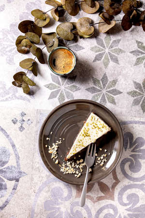 Piece of raw vegan cheesecake, no bake gluten free, decorated by lime zest and cashew nuts on plate. Cup of black coffee and Eucalyptus branches on ornate ceramic table. Sunlight. Flat lay Stok Fotoğraf
