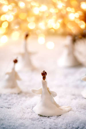Porcelain Christmas angels. Set of craft handmade Christmas decoration on snow with bokeh holiday lights background.