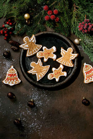 Homemade traditional Christmas gingerbread cookies with icing ornate. Gingerbread Man, angel, bell on ceramic plate with xmas decorations over dark background. Flat lay