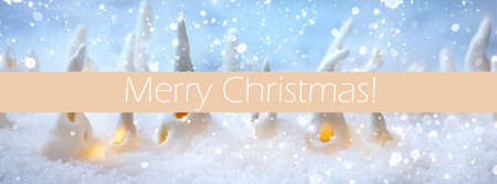 Porcelain Christmas houses. Set of craft handmade Christmas decoration houses with glowing windows on sparkling snow. Merry Christmas inscription over champagne color strip. Banner size
