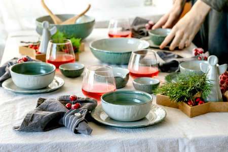 Rustic Christmas table setting with empty craft ceramic tableware, plates and bowls, xmas angel decorations, glasses of red juice, green branches and berries on white tablecloth in front of the window