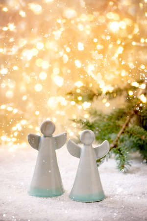 Ceramic Christmas angels. Set of two craft handmade Christmas decoration angels on snow with bokeh holiday lights and fir tree branches.