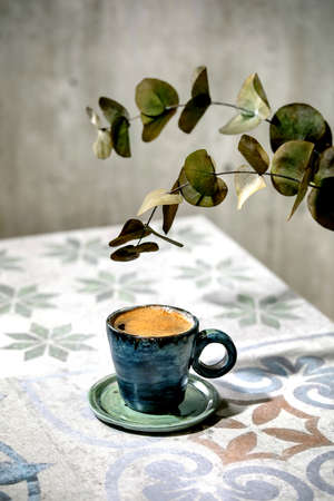 Cup of turkish black frothy coffee on ornate ceramic table with Eucalyptus branches. Sunlight Stok Fotoğraf