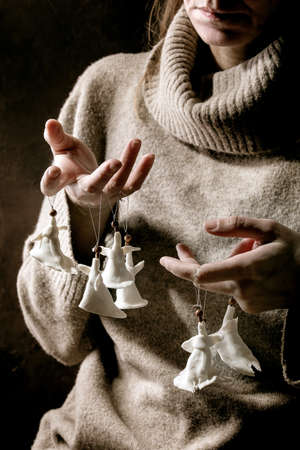 Porcelain Christmas angels. Woman in wool pullover hold on fingers set of white craft handmade Christmas angels decoration. Dark background.