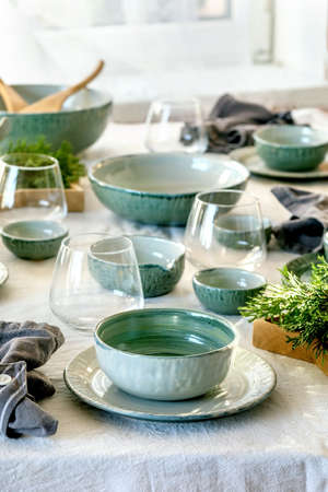 Rustic Christmas table setting with empty craft ceramic tableware, plates and bowls, xmas angel decorations, glasses, green branches on white tablecloth in front of the window Stok Fotoğraf
