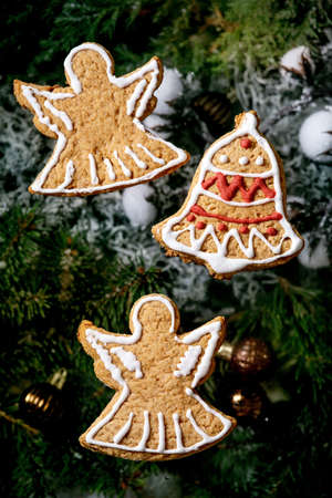 Homemade traditional Christmas gingerbread cookies with icing ornate. Gingerbread angels and bell with xmas decorations and fir tree as background. Flat lay
