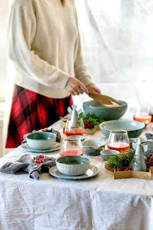 Rustic Christmas table setting with empty craft ceramic tableware, plates and bowls, xmas angel decorations on white tablecloth in front of the window. Woman hold a salad bowl