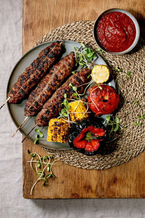 Eastern fast food. Grilled spicy beef lyulya kebab on sticks on plate with grilled vegetables sweet corn cob, tomato and paprika, tomato sauce on wooden table. Flat lay Stok Fotoğraf