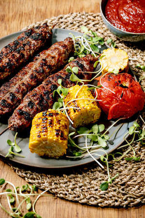 Eastern fast food. Grilled spicy beef lyulya kebab on sticks on flat bread with grilled vegetables sweet corn cob, tomato and paprika, tomato sauce on wooden table. Stok Fotoğraf