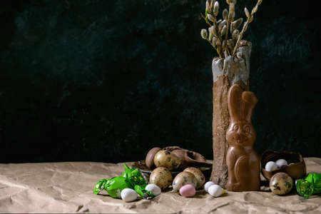 Easter mood still life with blossom willow branches in ceramic vase, traditional chocolate rabbit, eggs and sweets on table with crumpled craft paper. Dark background. Stok Fotoğraf