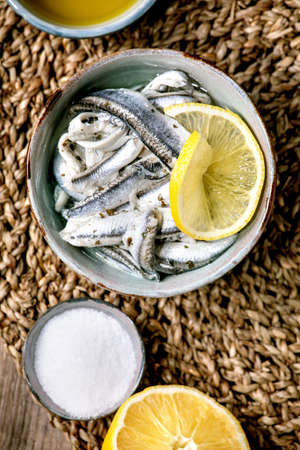 Bowl of pickled anchovies or sardines fillet in oil, served with lemon, olive oil, salt for tapas or antipasti over old wooden background. Flat lay, copy space
