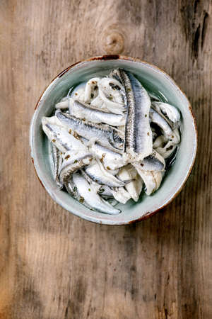 Bowl of pickled anchovies or sardines fillet in oil with herbs for tapas or antipasti over old wooden background. Flat lay, copy space