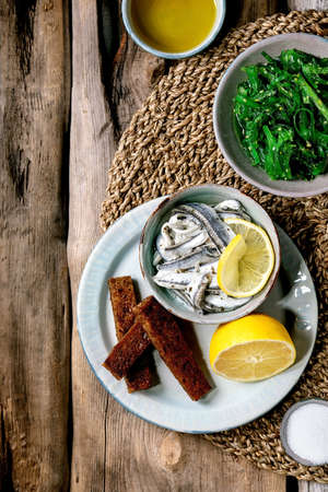Bowl of pickled anchovies or sardines fillet in oil, served with lemon, olive oil, salt and toasted rye bread for tapas or antipasti, Wakame seaweed salad on old wooden background. Flat lay. Stok Fotoğraf