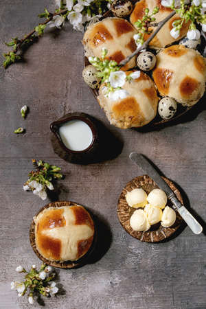 Homemade Easter traditional hot cross buns on ceramic plate with blossom cherry branches, butter, jug of milk over brown texture background. Flat lay, space