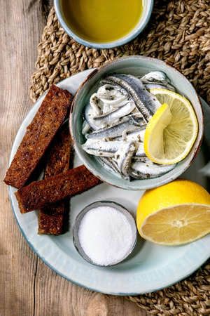 Bowl of pickled anchovies or sardines fillet in oil, served with lemon, olive oil, salt and toasted rye bread for tapas or antipasti over old wooden background. Flat lay, copy space