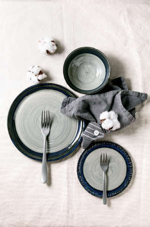 Set of empty gray ceramic plates with forks and textile napkin, decorated by cotton flowers over white linen tablecloth. Table setting. Flat lay, space. Stok Fotoğraf