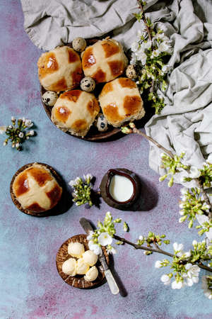 Homemade Easter traditional hot cross buns on ceramic plate with blossom cherry branches, butter, jug of milk, textile over blue texture background. Flat lay, space