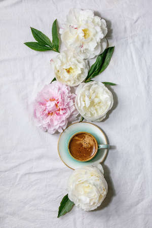 Cup of espresso coffee, pink and white peonies flowers with leaves over white cotton textile background. Flat lay, copy space