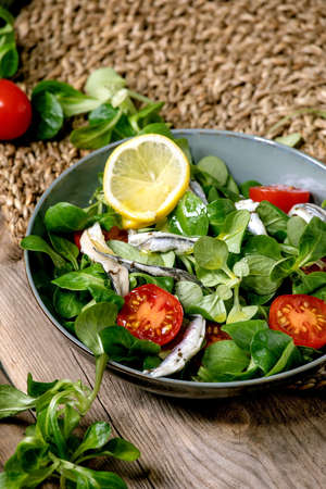 Green field salad with pickled anchovies or sardines fillet, and cherry tomatoes, served in blue bowl with lemon and olive oil on straw napkin over old wooden table.