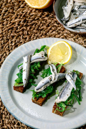 Appetizers tapas pickled anchovies or sardines fillet Wakame seaweed salad on toasted rye bread, served on blue plate with lemon on straw napkin as background.