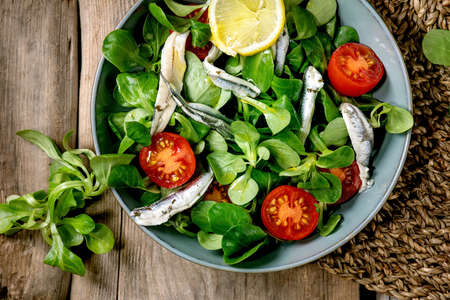 Green field salad with pickled anchovies or sardines fillet, and cherry tomatoes, served in blue bowl with lemon and olive oil on straw napkin over old wooden background. Flat lay, space