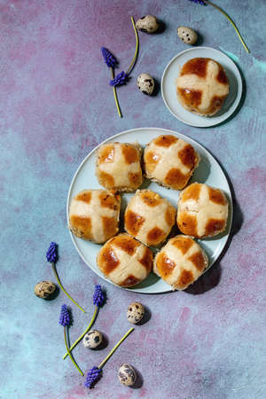 Homemade Easter traditional hot cross buns on ceramic plate with muscari flowers, quail eggs, textile over blue texture background. Flat lay, space Stock fotó