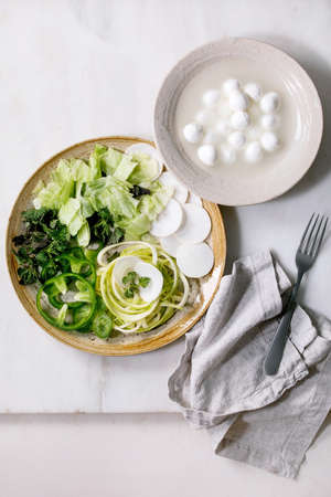 Fresh green raw vegetables and herbs spaghetti zucchini, white radish, green paprika, ice salad, mozzarella balls for cooking dinner salad. Ceramic plate on white marble table. Flat lay, copy space