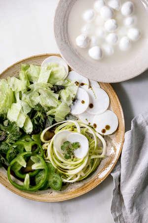 Fresh green raw vegetables and herbs spaghetti zucchini, white radish, green paprika, ice salad, mozzarella balls for cooking dinner salad.
