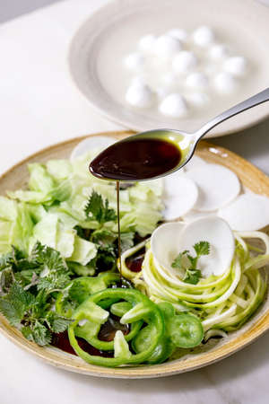 Pouring pumpkin seed oil on fresh green raw vegetables and herbs, spaghetti zucchini, white radish, green paprika, ice salad, mozzarella balls for cooking salad.