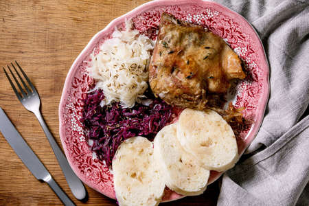 Baked duck legs with sliced boiled bread knedliks, sauerkraut in ceramic plate, decorated with napkin over brown wooden background. Traditional Czech, German and european cuisine. Top view, flat lay