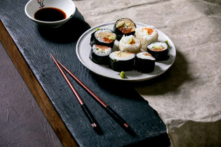 Homemade sushi rolls set with salmon, japanese omelette, avacado, wasabi and soy sauce with wooden chopsticks on grey paper over black wooden table. Japanese style dinner 版權商用圖片