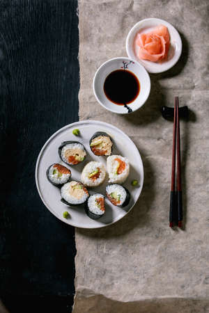 Homemade sushi rolls set with salmon, japanese omelette, avacado, ginger, wasabi and soy sauce with chopsticks on grey paper over black wooden background. Top view, flat lay. Japanese style dinner